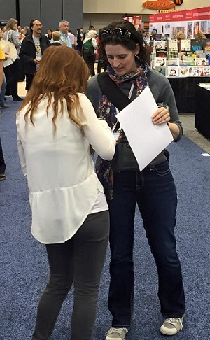 IBPA project coordinator Mimi Le (left) scans the badge of a visiting librarian during the 2015 ALA Annual Conference